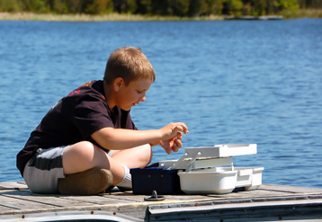 child on dock with fishing tackle